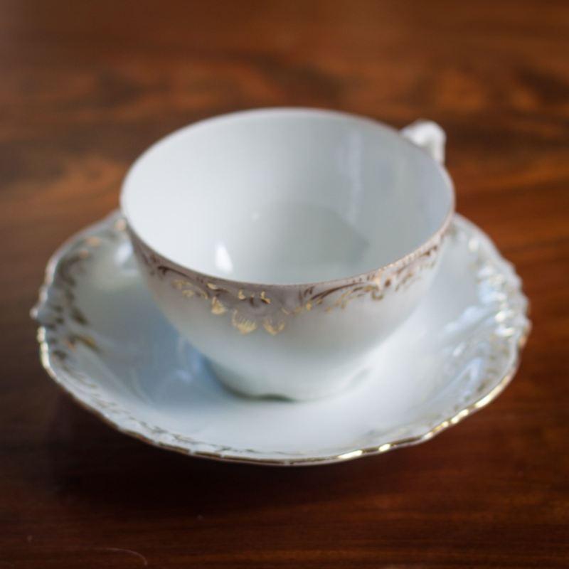 vit tekopp med guldkant