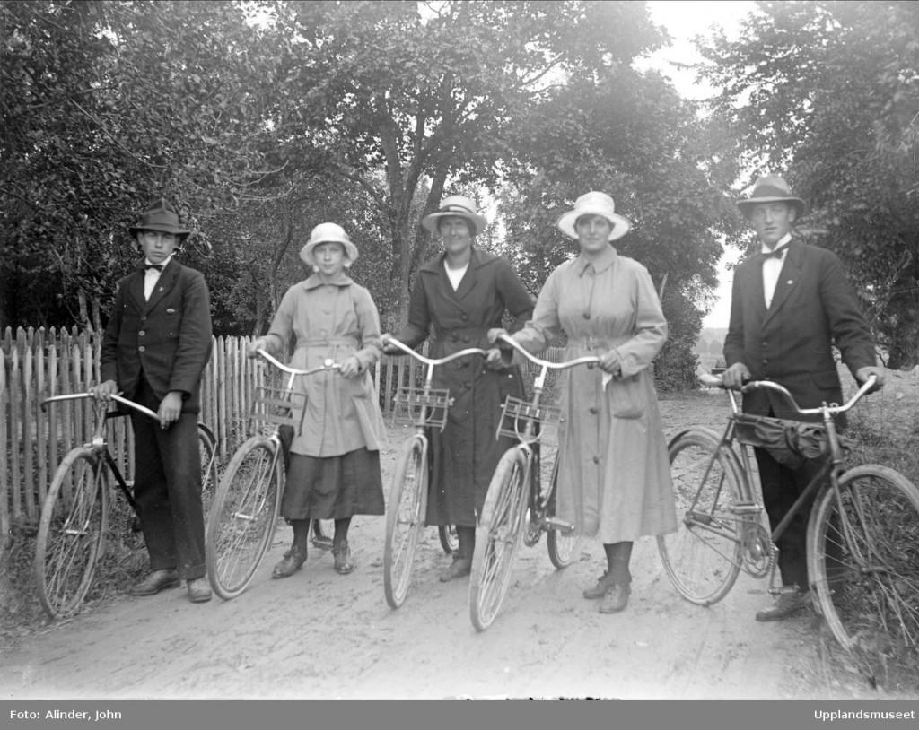 """Svartvitt foto av Edvin och Valborg Söderlund med släktingar""""stående med cyklarna"""", Ådalen, Altuna socken, Uppland 1920. Foto: Alinder, John / Upplandsmuseet CC BY-NC-ND"""