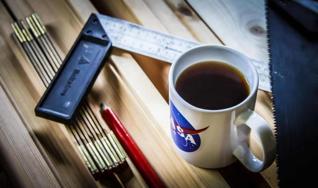Brädor med en mugg te, verktyg och en vinkelhake